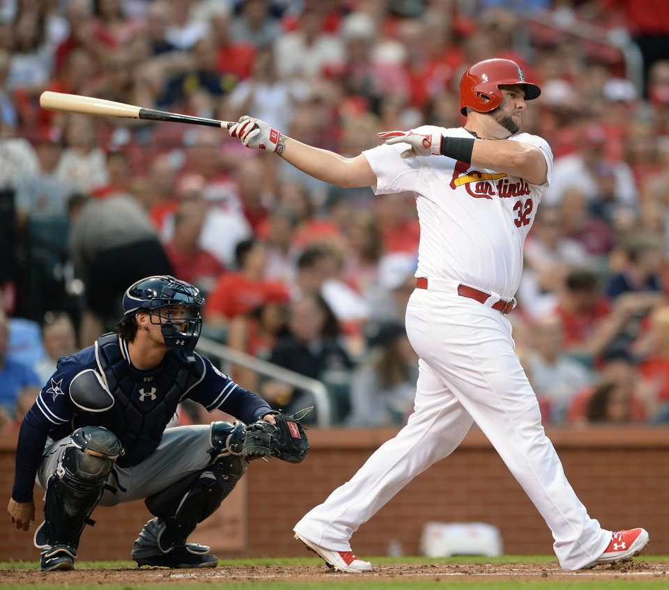 Photo - St. Louis Cardinals' Matt Adams (32) singles as San Diego Padres' Yasmani Grandal, left, watches in the second inning in a baseball game, Thursday, Aug. 14, 2014, at Busch Stadium in St. Louis. (AP Photo/Bill Boyce)
