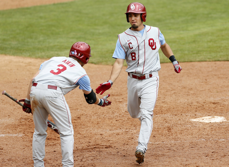 Photo - OU's Jack Mayfield (8) and Craig Aikin (3) celebrate after they both scored in the 9th inning  during an NCAA baseball game between Oklahoma and Texas Tech in the Big 12 Baseball Championship tournament at the Chickasaw Bricktown Ballpark in Oklahoma City, Friday, May 24, 2013. OU won 8-0. Photo by Nate Billings, The Oklahoman