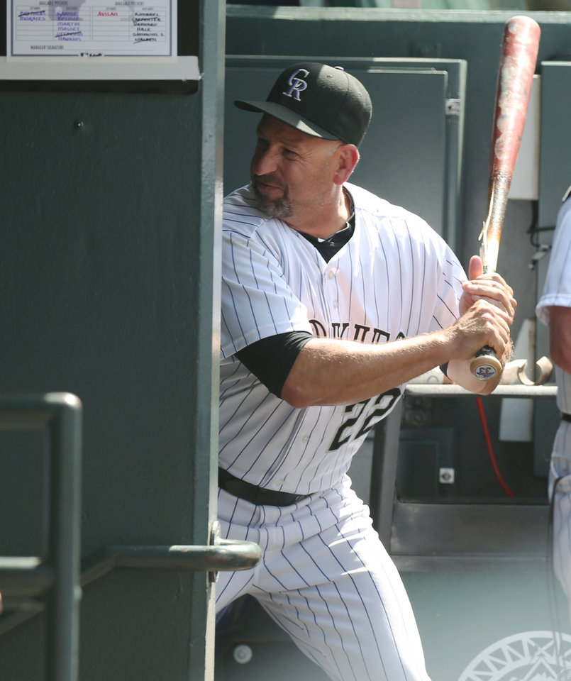 Photo - Upset over being ejected from the game, Colorado Rockies manager Walt Weiss smashes a bat into the wall by the bat rack in the Rockies' dugout on the way to the showers against the Atlanta Braves in the eighth inning of the Rockies' 10-3 victory in a baseball game in Denver on Thursday, June 12, 2014. Weiss was ejected after arguing about the Rockies' Corey Dickerson getting hit by a pitch thrown by Braves relief pitcher David Carpenter. (AP Photo/David Zalubowski)
