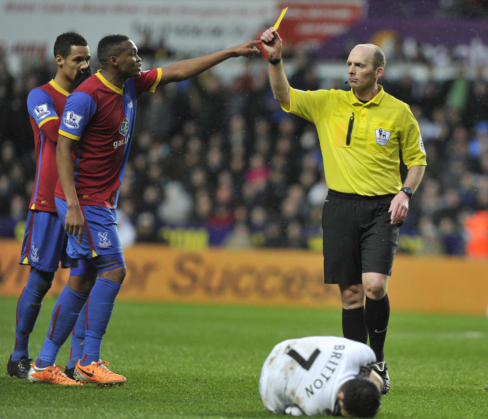 Photo - Referee Mike Dean, right, shows a yellow card to Crystal Palace's Mile Jedinak, not pictured, during the English Premier League soccer match between Swansea City and Crystal Palace at the Liberty Stadium, Swansea, Wales, Sunday, March 2, 2014. (AP Photo/PA)   UNITED KINGDOM OUT   -   NO SALES   -  NO ARCHIVES