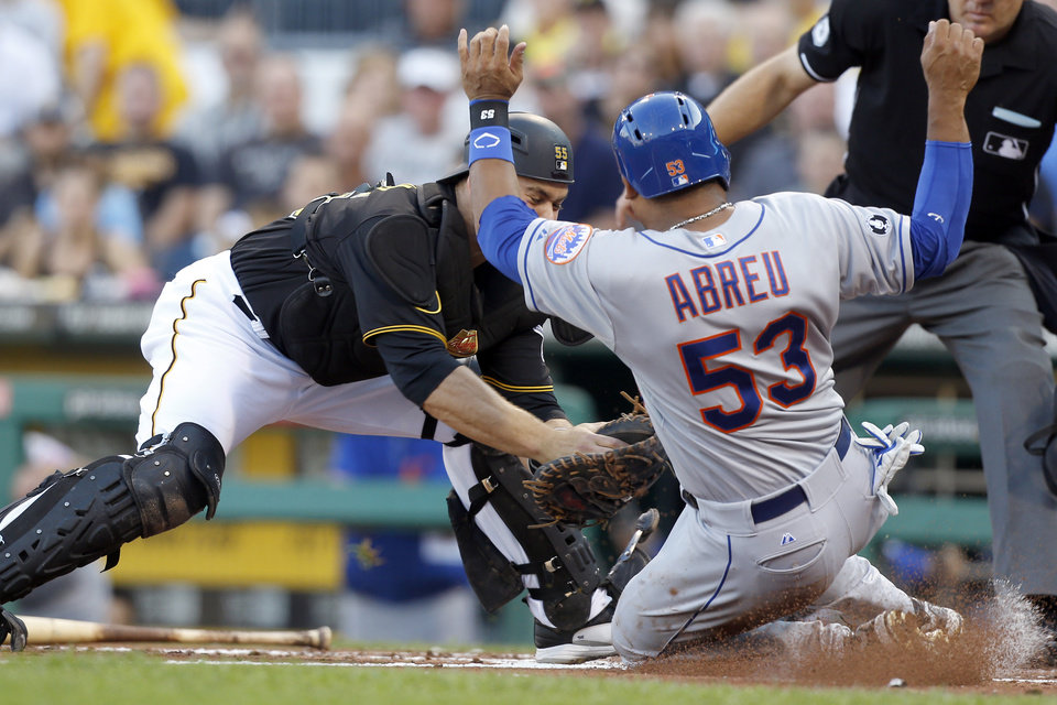 Photo - Pittsburgh Pirates catcher Russell Martin, left, tags out New York Mets' Bobby Abreu for the third out as Abreu tried to score from second on a hit by Ruben Tejada in the second inning of a baseball game Thursday, June 26, 2014, in Pittsburgh. (AP Photo/Keith Srakocic)
