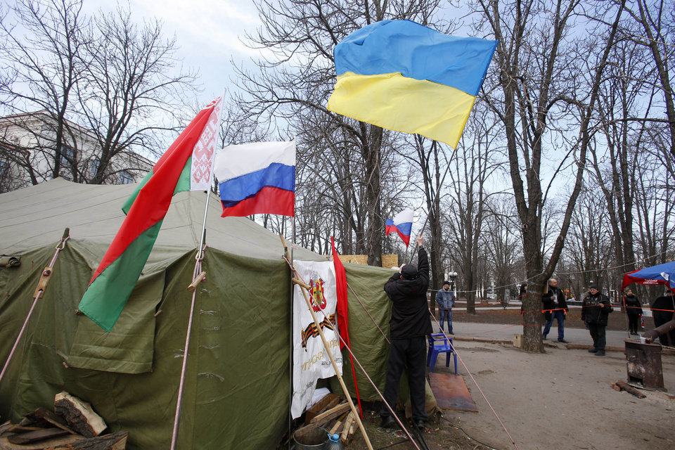 Photo - In this photo taken Tuesday, March 11, 2014, a man places a Ukrainian flag atop a tent alongside flags from Russia, center, and Belarus, left, at a tent camp set up by pro Russia activists in Luhansk, eastern Ukraine. Luhansk was home to one of the Soviet Union's blue-ribbon factories that turned out locomotives deemed good enough to be designated IS--the Russian-language initials of Josef Stalin. Since Russian troops rolled into Crimea, and lawmakers there scheduled a referendum for Sunday on whether to join Russia, the world's attention has focused on the fate of the lush peninsula that juts into the Black Sea. But here in Ukraine's coal-fired industrial east, where Russians have lived for more than two centuries, a potent mix of economic depression, ethnic solidarity and nostalgia for the certainties of the Soviet past have many demanding the right to become part of Russia as well.(AP Photo/Sergei Grits)