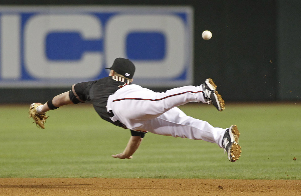 Photo - Arizona Diamondbacks second baseman Aaron Hill can't catch an RBI single by Cincinnati Reds' Todd Frazier during the fourth inning of a baseball game, Saturday, May 31, 2014, in Phoenix. (AP Photo/Ralph Freso)