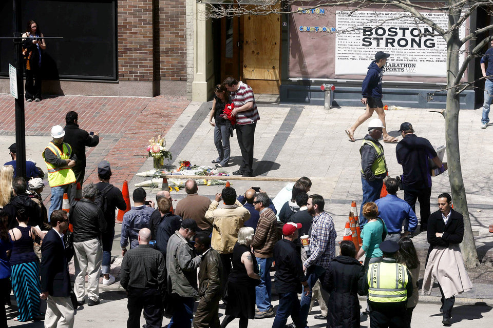 Photo - People gather at the site where the first bomb detonated on April 15 near the finish line of the Boston Marathon on Boylston Street in Boston, Wednesday, April 24, 2013. Traffic was allowed to flow all the way down Boylston Street on Wednesday morning for the first time since two explosions. (AP Photo/Michael Dwyer)
