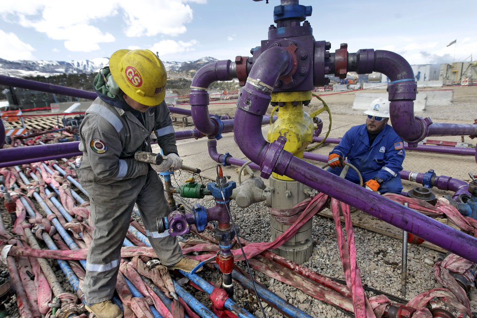 Photo - FILE - In this March 29, 2013 file photo, workers tend to a well head during a hydraulic fracturing operation at an Encana Oil & Gas (USA) Inc. gas well outside Rifle, in western Colorado. The Obama administration is proposing a rule that would require companies that drill for oil and natural gas on federal lands to publicly disclose chemicals used in hydraulic fracturing operations. The new