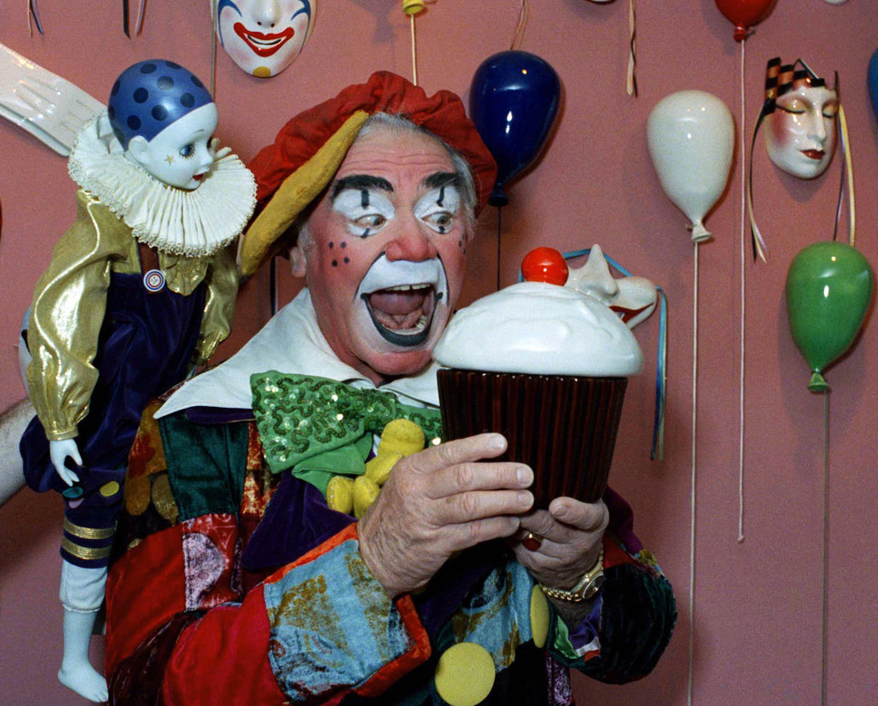 Photo - FILE - In this June 18, 1985, file photo, Ernest Borgnine holds a giant cupcake dressed as a clown in Los Angeles, for the revival of the Great Circus Parade in Milwaukee.  A spokesman said Sunday, July 8, 2012, that Borgnine has died at the age of 95. (AP Photo/Robert Gabriel, File) ORG XMIT: NY807