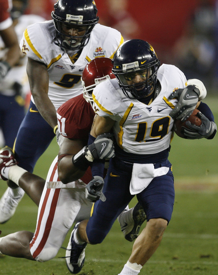 Photo - Vaughn Rivers is stopped by Demarrio Pleasant during the first half of the Fiesta Bowl college football game between the University of Oklahoma Sooners (OU) and the West Virginia University Mountaineers (WVU) at The University of Phoenix Stadium on Wednesday, Jan. 2, 2008, in Glendale, Ariz. 