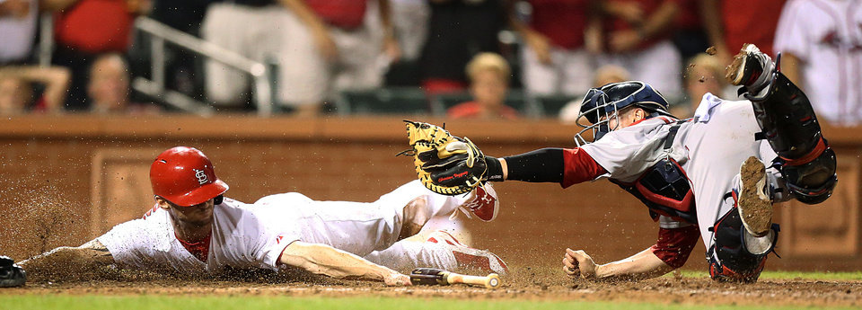 Photo - St. Louis Cardinals' Shane Robinson, left, scores past Boston Red Sox catcher Christian Vazquez during the seventh inning of a baseball game Tuesday, Aug. 5, 2014, in St. Louis. (AP Photo/St. Louis Post-Dispatch, Chris Lee)