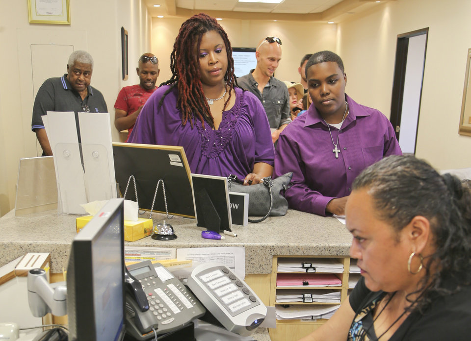 Photo - Rika Grier, left, and her partner Pastor Nicki Fairley, hear from Senior Assessment clerk Jennifer Samuela at the San Diego County marriage bureau while obtaining their license in San Diego, Monday, July 1, 2013. The pair have been together for six years.  (AP Photo/Lenny Ignelzi)