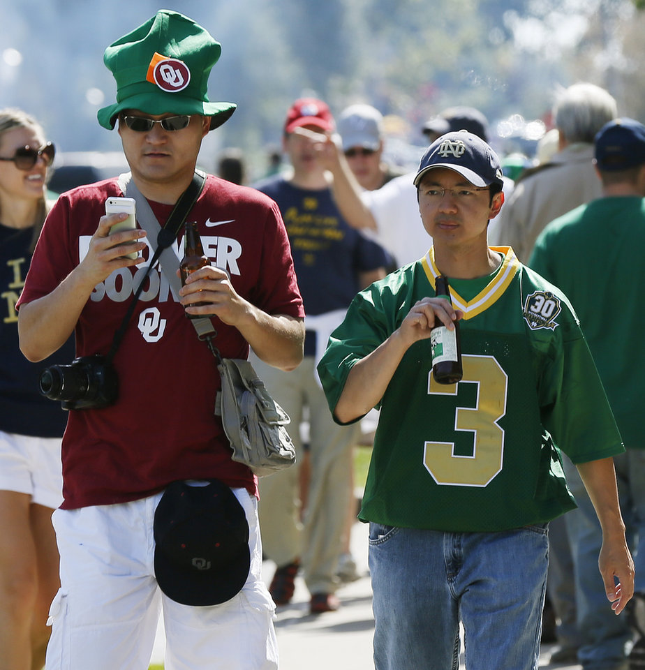 Photo - OU fan Charles Hutton, left, of Washington D.C., and Notre Dame fan Thien Le, of Chicago, walk to the stadium before a college football game between the University of Oklahoma Sooners (OU) and the Notre Dame Fighting Irish at Notre Dame Stadium in South Bend, Ind., Saturday, Sept. 28, 2013. Hutton is originally from Oklahoma City, while Le grew up in South Bend, Ind. Photo by Nate Billings, The Oklahoman