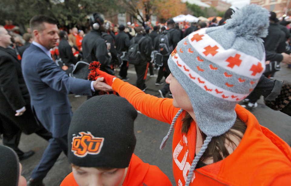 Photo - An Oklahoma State fan reaches out to touch coach Mike Gundy as he walks in the 'Spirit Walk' before the Bedlam college football game between the Oklahoma State University Cowboys (OSU) and the University of Oklahoma Sooners (OU) at Boone Pickens Stadium in Stillwater, Okla., Saturday, Dec. 3, 2011. Photo by Chris Landsberger, The Oklahoman