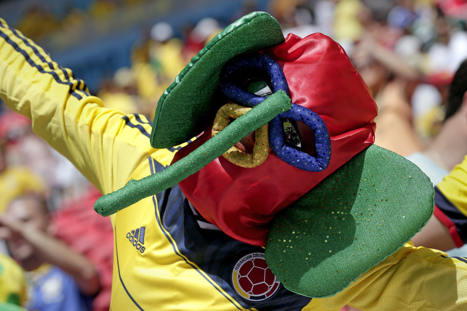 Photo - A Colombian supporter sports outrageous headwear before the group C World Cup soccer match between Colombia and Ivory Coast at the Estadio Nacional in Brasilia, Brazil, Thursday, June 19, 2014.  (AP Photo/Marcio Jose Sanchez)