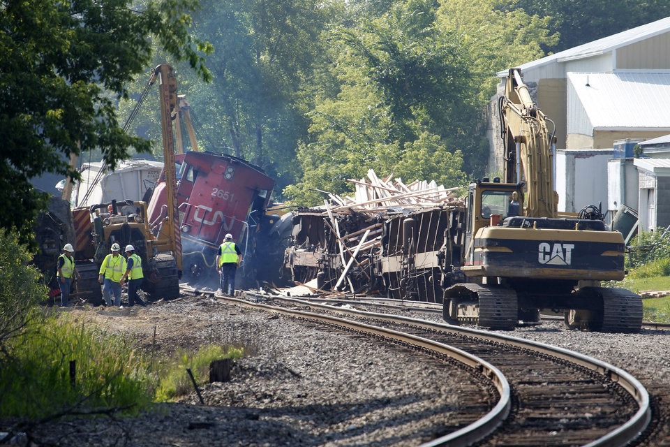 Photo - Workers clean up after a train derailment in Slinger, Wis., Monday, July 21, 2014. A southbound Canadian National train struck several Wisconsin & Southern Railroad cars around 8:30 p.m. Sunday at a rail crossing in Slinger, Wis., according to Patrick Waldron, a Canadian National spokesman. The derailment injured at least two people and spilled thousands of gallons of fuel that prompted the evacuation of dozens of homes, but evacuees were allowed to return around 1:30 a.m. Monday, Slinger Fire Chief Rick Hanke said. (AP Photo/Milwaukee Journal-Sentinel, Gary Porter)