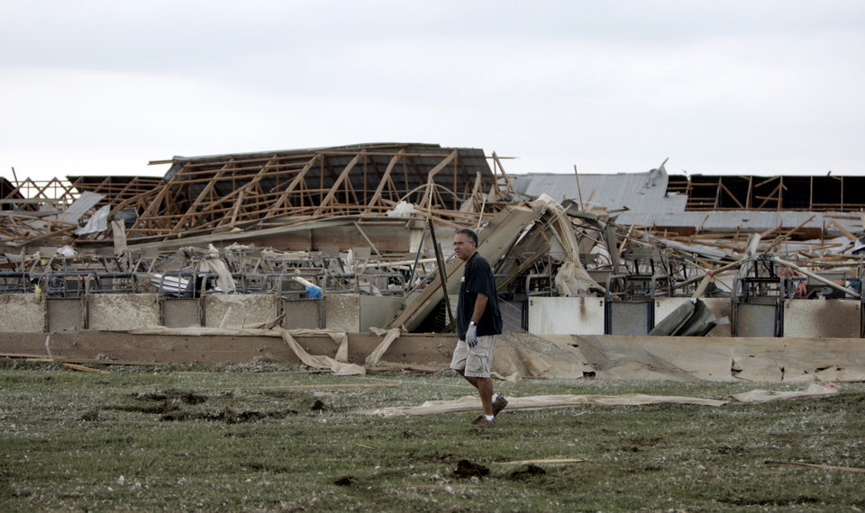 Baz Warner walks in front of damaged buildings at Farm 62 of Seaboard Foods near Lacey, Okla., Saturday, May 24, 2008. The farm was severely damaged by a tornado. BY SARAH PHIPPS, THE OKLAHOMAN