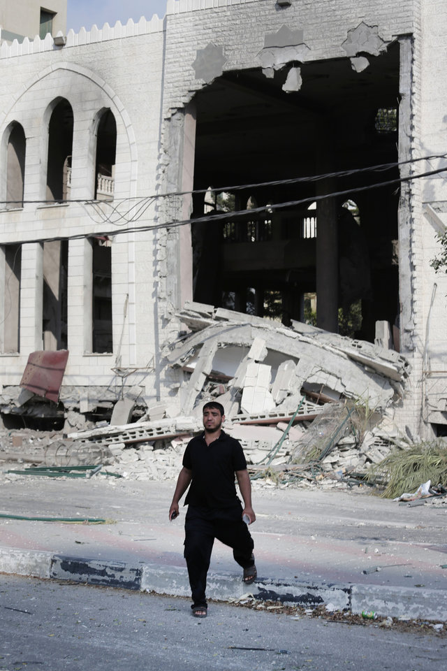 Photo - A Palestinian walks past the Ameen mosque in Gaza City, northern Gaza Strip, destroyed by an Israeli strike, Tuesday, July 29, 2014. Early Tuesday, Israel warplanes struck a series of targets in Gaza City, including the top Hamas leader in Gaza, Ismail Haniyeh's house and government offices, while Gaza's border area with Israel was hit by heavy tank shelling. (AP Photo/Lefteris Pitarakis)