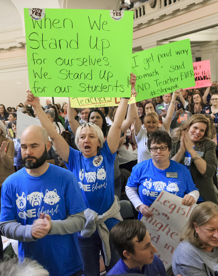 Photo - Edmond Public School teacher Wendy Joseph, center, holds up a sign as she gathers with other teachers during a rally to support the Step Up Oklahoma Plan at the state capitol in Oklahoma City, Okla. on Monday, Feb. 12, 2018.    Photo by Chris Landsberger, The Oklahoman