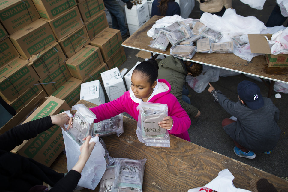 Photo -   9-year-old Sidney, no last name available, helps bag Meals-Ready-to-Eat (MREs) for distribution to the residents of the Lower East Side who remain without power due to Superstorm Sandy, Friday, Nov. 2, 2012, in New York. In Manhattan, where 226,000 buildings, homes and business remain without power, Consolidated Edison says they should have service restored by Saturday. (AP Photo/ John Minchillo)