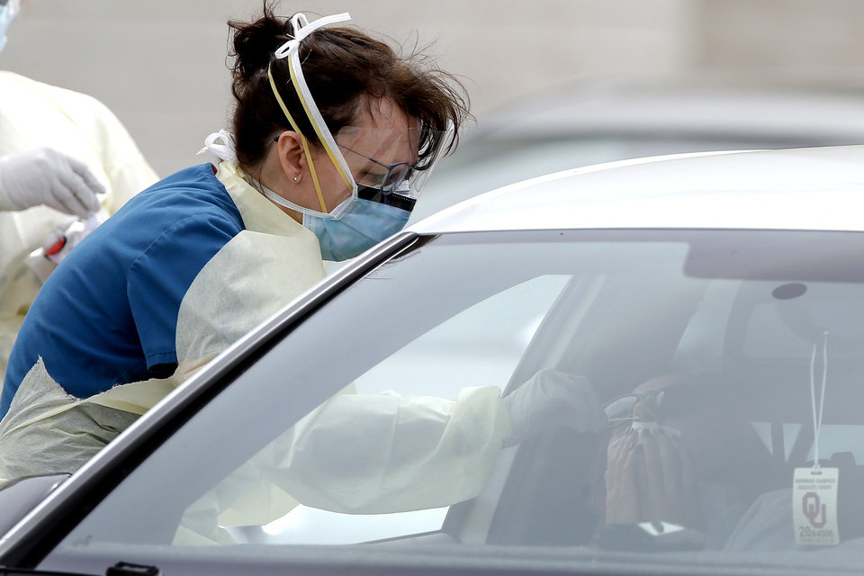 Photo - A Cleveland County Health Department employee uses a swab to collect a sample from a person inside a car at a COVID-19 drive-thru testing site at Griffin Community Park in Norman, Okla., Thursday, April 9, 2020. [Bryan Terry/The Oklahoman]