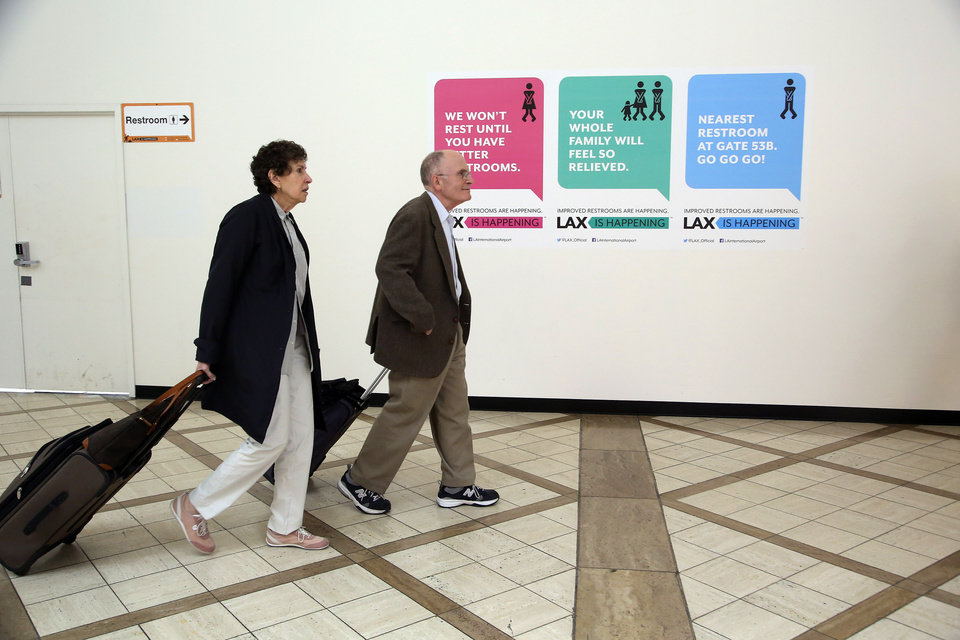 Photo - In this Monday, May 5,  2014 photo passengers walk at the Delta Airlines terminal, under renovation at Los Angeles International Airport (LAX). The aging airport is scheduled to get newly surfaced roads, upgraded restaurants with Los Angeles themes, and some terminal makeovers that will infuse more sunlight into otherwise cave-like interiors. Also in the plans are new bathrooms and, that essential for travelers, more outlets and USB ports for charging electronic devices. (AP Photo/Nick Ut )