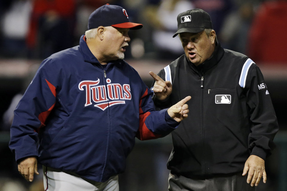 Photo -   Minnesota Twins manager Ron Gardenhire, left, argues with umpire Joe West in the eighth inning of a baseball game against the Cleveland Indians, Wednesday, Sept. 19, 2012, in Cleveland. A line drive by Joe Mauer was initially ruled a single, but the umpiring crew met and concluded Cleveland Indians left fielder Vinny Rottino made the catch. (AP Photo/Mark Duncan)