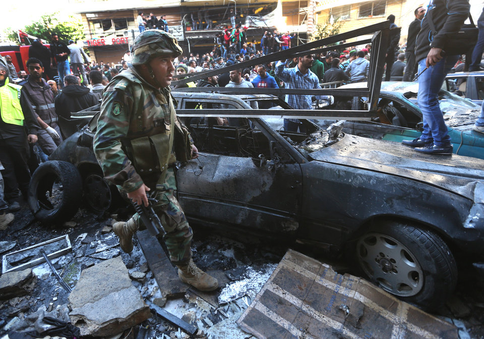 Photo - A Lebanese army soldier passes next to a burned car at the site of an explosion in a stronghold of the Shiite Hezbollah group, in the southern suburb of Beirut, Lebanon, Tuesday, Jan. 21, 2014. A car bomb ripped through a Shiite neighborhood in southern Beirut on Tuesday, killing several people and setting plumes of smoke over the area in the latest attack targeting supporters of the militant Hezbollah group in Lebanon. (AP Photo/Hussein Malla)