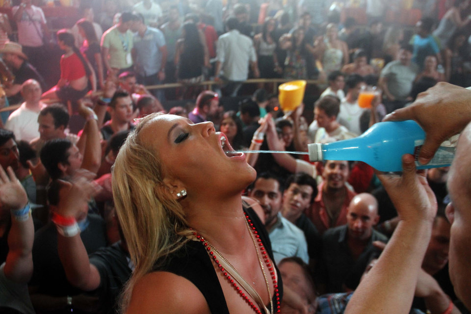 A spring break reveler gets a drink at a bar in the resort city of Cancun, Mexico, early Tuesday Feb. 26, 2013. Cancun is one of the No. 1 foreign destination for U.S. college students wanting to enjoy Spring Break. (AP Photo/Israel Leal)