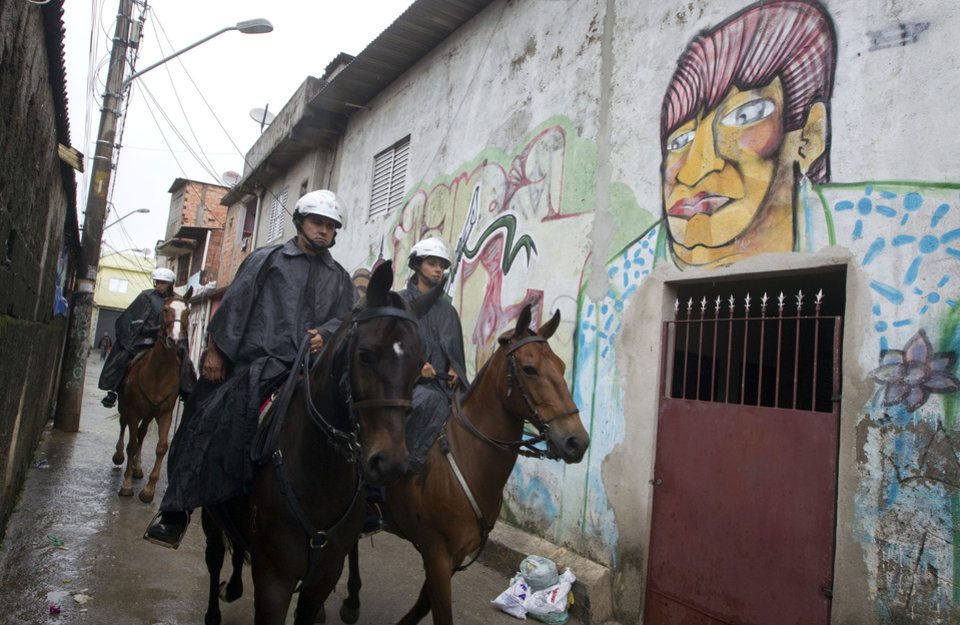 Mounted military police patrol in the Paraisopolis slum of Sao Paulo, Brazil, early Tuesday, Nov. 13, 2012. At least 140 people have been murdered in South America\'s biggest city over the past two weeks in a rising wave of violence, Sao Paulo\'s Public Safety Department said on Sunday. (AP Photo/Andre Penner)