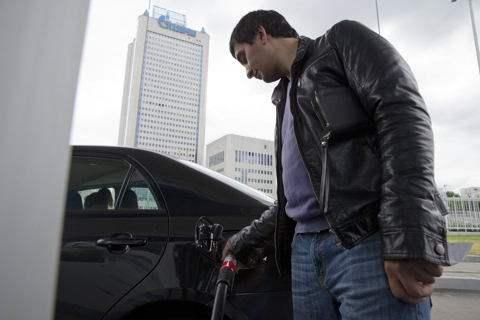 Photo - A man fuels his car with the headquarters of Russia's state-run natural gas giant Gazprom in the background, in Moscow, Russia, Monday, June 16, 2014. Russia said on Monday it would cut off gas supplies to Ukraine as a payment deadline passed and negotiators failed to reach a deal on gas prices. Gazprom spokesman Sergei Kupriyanov said Moscow had no legal grounds to supply Ukraine with any more gas because Ukraine had not paid its bills. (AP Photo/Pavel Golovkin)