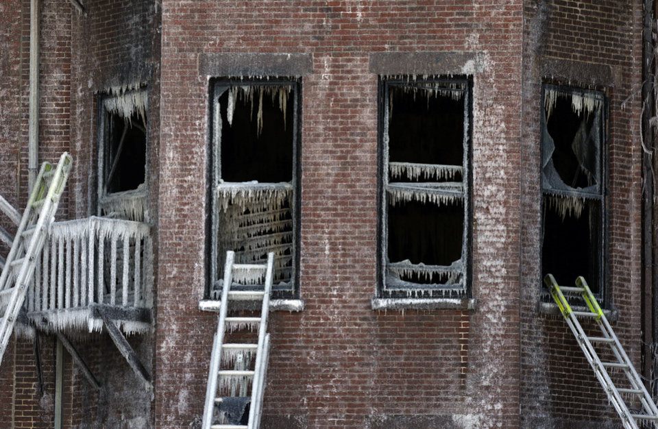 Photo - Ladders lean against burned remains of a four-story brownstone, Thursday, March 27, 2014, in Boston. Two firefighters, Lt. Edward Walsh and Michael Kennedy, lost their lives fighting a nine-alarm blaze that destroyed the structure in Boston's Back Bay neighborhood Wednesday, March 26, 2014. (AP Photo/Steven Senne)