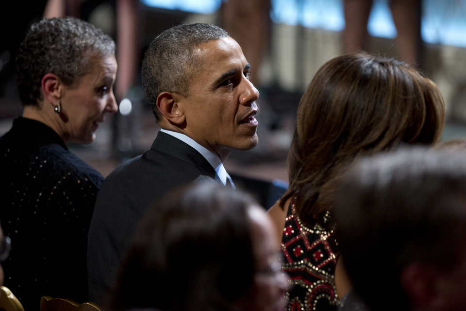 Photo - President Barack Obama, center, is flanked by first lady Michelle Obama, right, and Sharon Malone, wife of Attorney General Eric Holder, as they watch the