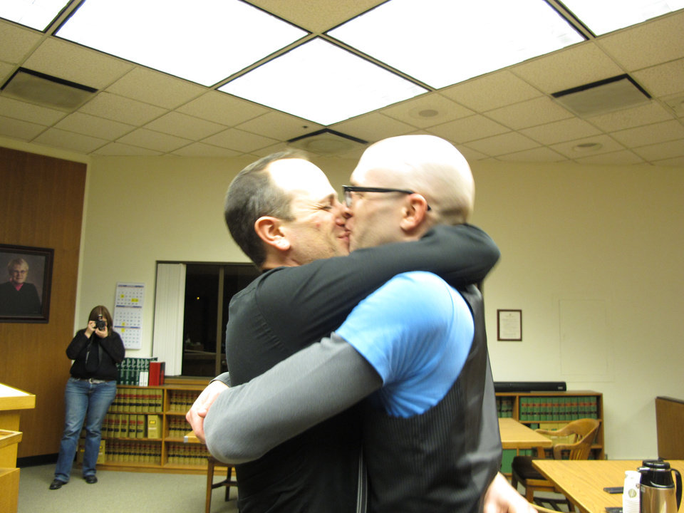 Photo - Matthew Wiltse, right, and Jonathon Bashford, left, kiss after they took their wedding vows at the Thurston County Courthouse just after midnight on Sunday, Dec. 9, 2012, in Olympia, Wash. Sunday is the first day same-sex couples can marry under Washington state's new voter-approved law allowing gay marriage. (AP Photo/Rachel La Corte)
