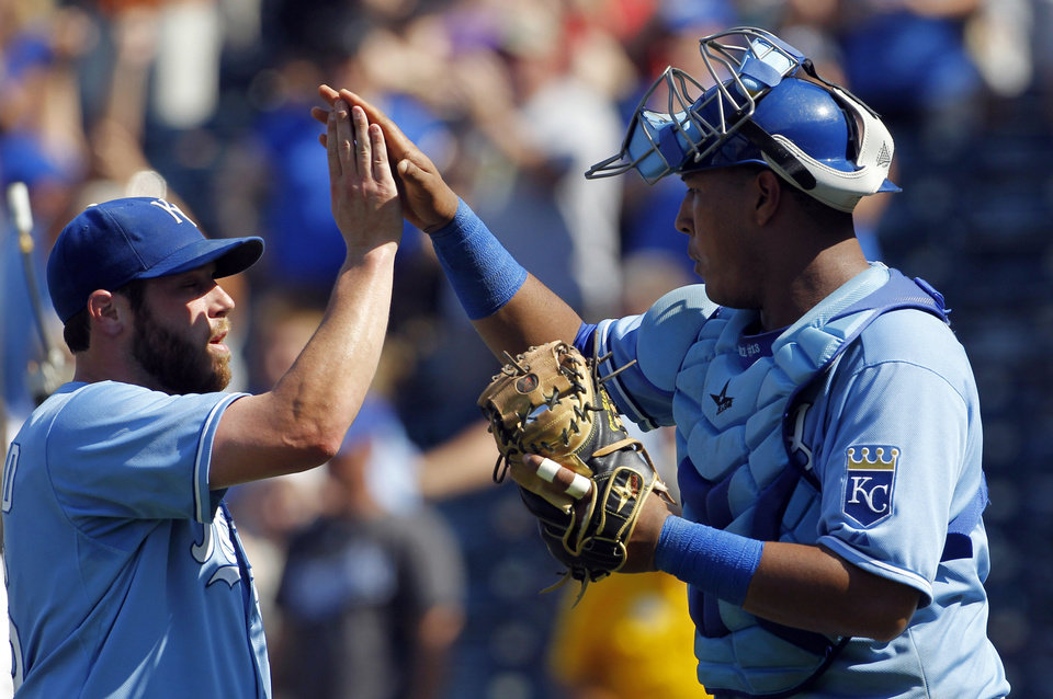 Photo - Kansas City Royals relief pitcher Greg Holland, left, and catcher Salvador Perez, right, celebrate their 6-4 win over the Washington Nationals at the end of a baseball game at Kauffman Stadium in Kansas City, Mo., Sunday, Aug. 25, 2013. (AP Photo/Colin E. Braley)