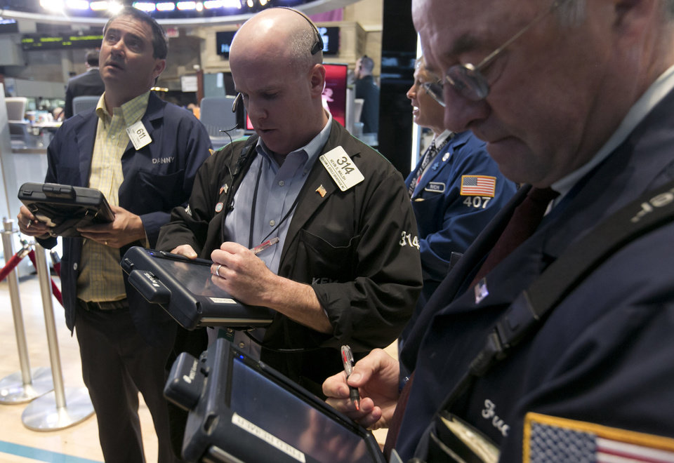 Photo - Traders work on the floor of the New York Stock Exchange Friday, May 30, 2014. Two negative reports on U.S. consumers were pushing stocks lower in early trading Friday. (AP Photo/Richard Drew)