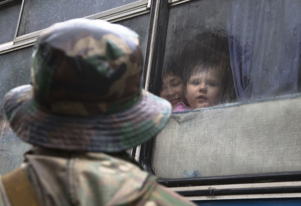 Photo - A Donetsk People's Republic fighter near a bus with his family departing as refugees to Russia in the city of Donetsk, eastern Ukraine Monday, July 14, 2014. Five busloads of Internally Displaced People from the towns of Slavyansk, Karlovka, Maryinka and Donetsk left here Monday morning for the Rostov region in Russia to ask for refugee status there. (AP Photo/Dmitry Lovetsky)