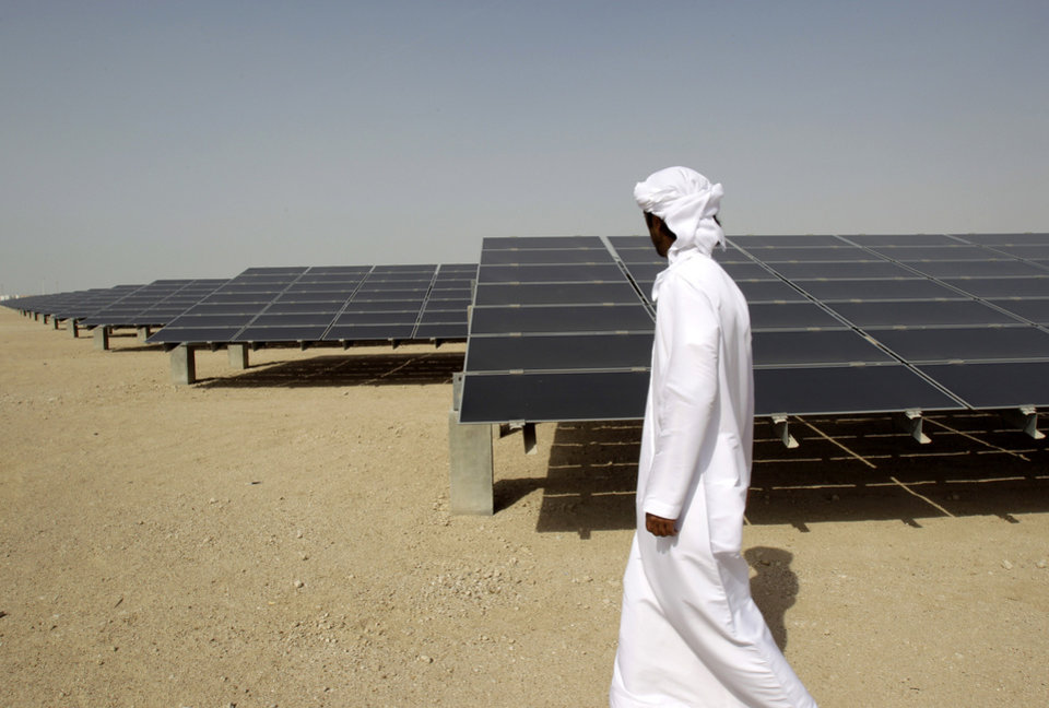 Photo - FILE - In theis Sunday, Jan. 16, 2011 file photo, an Emirati man pass by 10mw photovoltaic plant at Masdar City in Abu Dhabi, United Arab Emirates. The dean of a research institute at the core of Abu Dhabi's green-energy city said Sunday the government remains firmly committed to renewable power after recent shifts in the ambitious project's goals. Masdar City was originally conceived as a self-contained