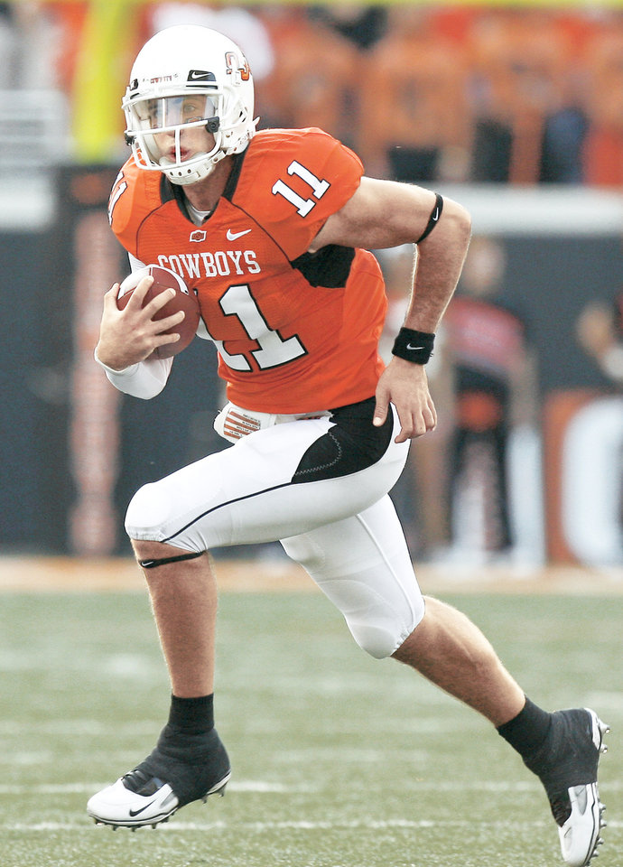 Photo - OSU's Zac Robinson scrambles during Saturday's game against Rice at Boone Pickens Stadium in Stillwater.  Photo by Sarah Phipps, The Oklahoman