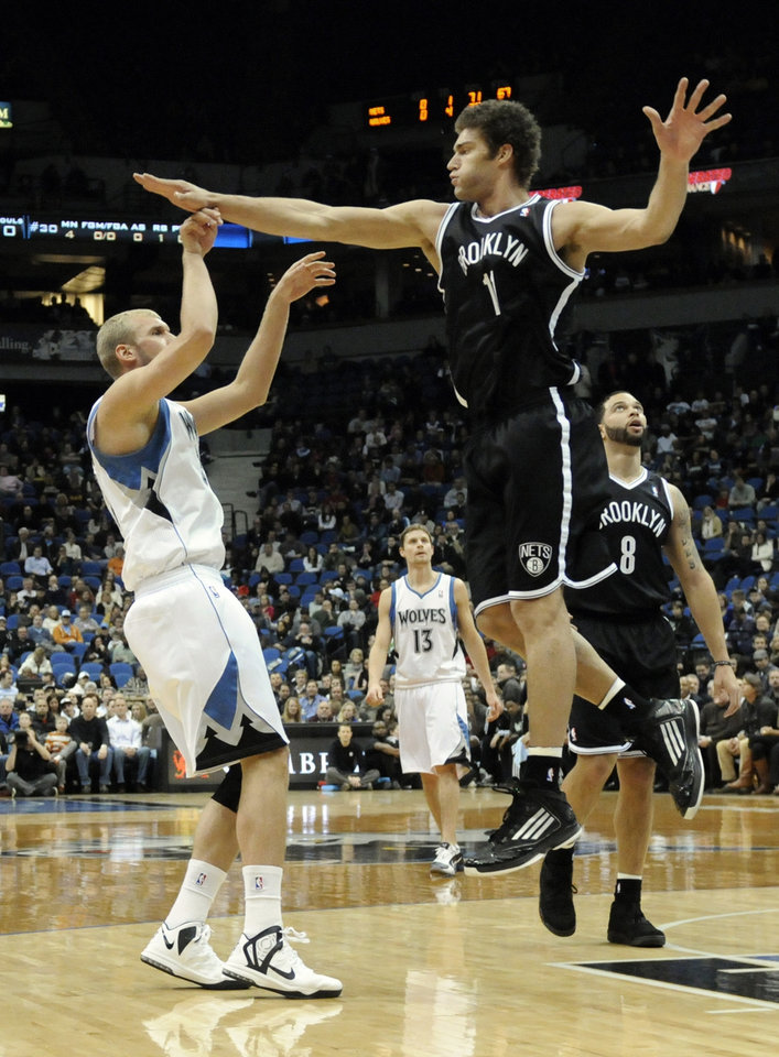Photo - Brooklyn Nets' Brook Lopez, right, hits Minnesota Timberwolves' Greg Stiemsma's hand while trying to block a shot in the first half of an NBA basketball game on Wednesday, Jan. 23, 2013, in Minneapolis. (AP Photo/Jim Mone)