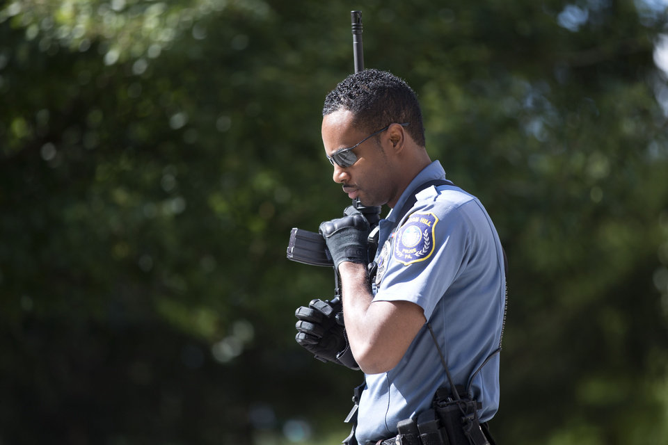 Photo - A police officer carries his weapon near the scene of a shooting at the Mercy Fitzgerald Hospital in Darby, Pa. on Thursday, July 24, 2014. A prosecutor said a gunman opened fire inside the psychiatric unit leaving one hospital employee dead and a second injured before being critically wounded himself. (AP Photo)