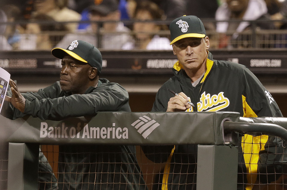 Photo - Oakland Athletics manager Bob Melvin, right, and batting coach Chili Davis watch from the dugout during the third inning of a spring exhibition baseball game against the San Francisco Giants in San Francisco, Friday, March 28, 2014. (AP Photo/Jeff Chiu)