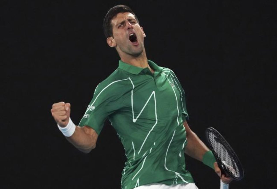 Photo -  Serbia's Novak Djokovic celebrates after winning the first set against Canada's Milos Raonic during their quarterfinal match at the Australian Open on Tuesday. [AP Photo/Lee Jin-man]