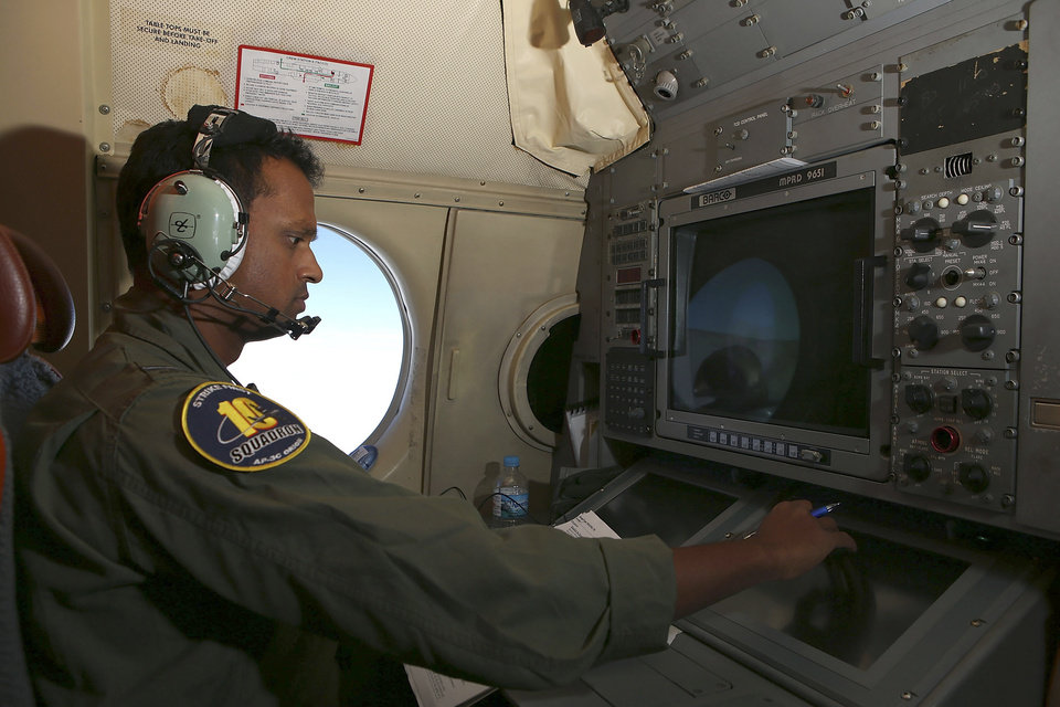Photo - In this Wednesday, March 26, 2014 photo, Tactical Coordinator Imray Cooray operates from his station on board a Royal Australian Air Force AP-3C Orion during a search for the missing Malaysia Airlines Flight 370 in the southern Indian Ocean. A French satellite scanning the Indian Ocean for remnants of the missing jetliner found a possible plane debris field containing 122 objects, a top Malaysian official said Wednesday, calling it