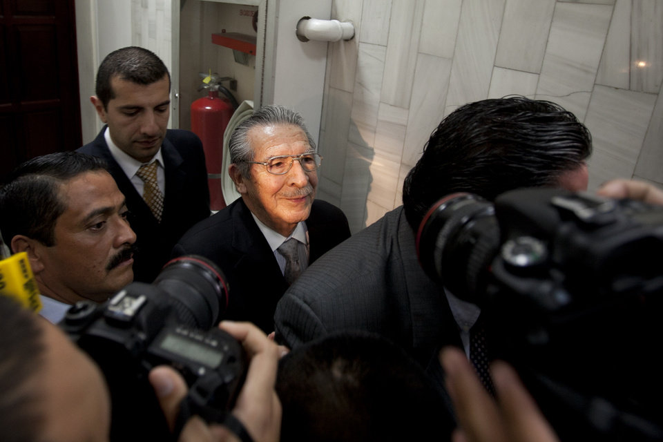 Guatemala's former dictator Jose Efrain Rios Montt, third from left, leaves after attending his hearing in Guatemala City, Monday, Jan. 28, 2013. Rios Montt, a former U.S.-backed dictator who presided over one of the bloodiest periods of Guatemala's civil war, will stand trial on charges he ordered the murder, torture and displacement of thousands of Mayan Indians, a judge ruled Monday. (AP Photo/Moises Castillo)