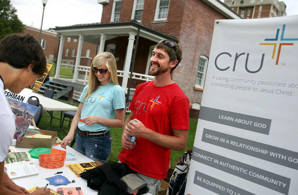 Photo -       Nate Tunnell, minister and director of Cru, right, and Stephanie Knight, chat with incoming student Tyler Smith at the University of Utah in Salt Lake City on Friday, Aug. 22, 2014. (Laura Seitz, Deseret News)