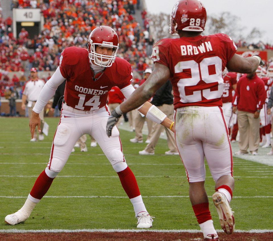 Photo - BEDLAM: Oklahoma's Sam Bradford (14) and Chris Brown (29) celebrate after Brown's touchdown during the first half of the college football game between the University of Oklahoma Sooners (OU) and the Oklahoma State University Cowboys (OSU) at the Gaylord Family -- Oklahoma Memorial Stadium on Saturday, Nov. 24, 2007, in Norman, Okla.   Photo By CHRIS LANDSBERGER, The Oklahoman ORG XMIT: KOD
