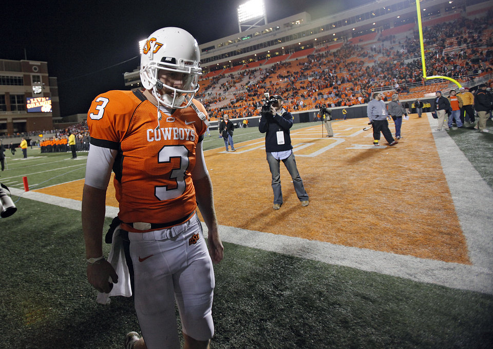 Photo - Oklahoma State's Brandon Weeden walks off the field after the Cowboys 47-41 loss to Oklahoma during the Bedlam college football game between the University of Oklahoma Sooners (OU) and the Oklahoma State University Cowboys (OSU) at Boone Pickens Stadium in Stillwater, Okla., Saturday, Nov. 27, 2010. Photo by Chris Landsberger, The Oklahoman