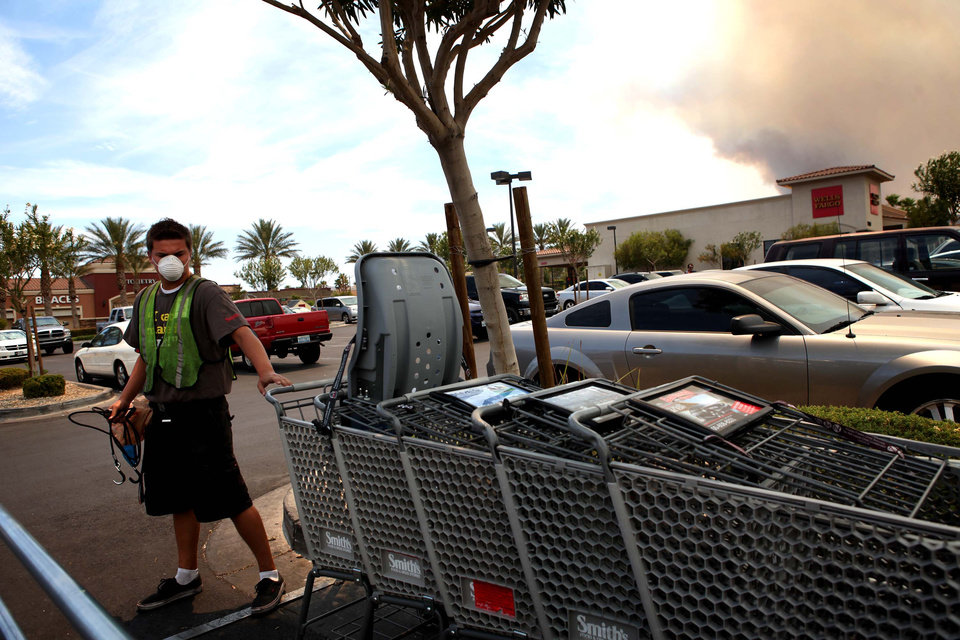 Photo - Jason Moore, 17, wears a mask protect to himself from the smoke produced by the Carpenter 1 fire, seen in background at right, while working in northwest Las Vegas Tuesday, July 9, 2013. The wildfire, which has grown to 19,000 acres, began July 1. (AP Photo/Las Vegas Review-Journal, Jessica Ebelhar)