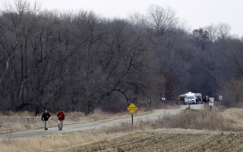 Photo - Law enforcement officials walk down a gravel road near the Seven Bridges Wildlife Area, Thursday, Dec. 6, 2012, in Readlyn, Iowa. Family members of missing cousins Lyric Cook, 10, and Elizabeth Collins, 8, who disappeared in July while riding their bikes in Evansdale, Iowa, are waiting to hear whether the two bodies discovered by hunters in the park on Wednesday are the two missing girls. (AP Photo/Charlie Neibergall)