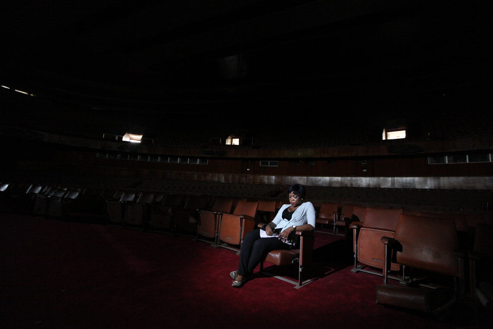 Photo - A worker sits in the abandoned bowl theater of Nigeria's National Theatre in Lagos, Nigeria, on Thursday, April 4, 2013. Nigeria's iconic National Theatre, long in disrepair, is now at the center of a massive redevelopment plan that could be worth millions of dollars.  Nigeria's federal government has plans to use money leasing the swampy land in Lagos around the theater to private investors so they can build a mall, a five-star hotel and other amenities. However, some have doubts that the project will actually raise money for the theater. Meanwhile, the plans have already likely encouraged local officials to demolish the homes of slum dwellers living around the theater. (AP Photo/Jon Gambrell)