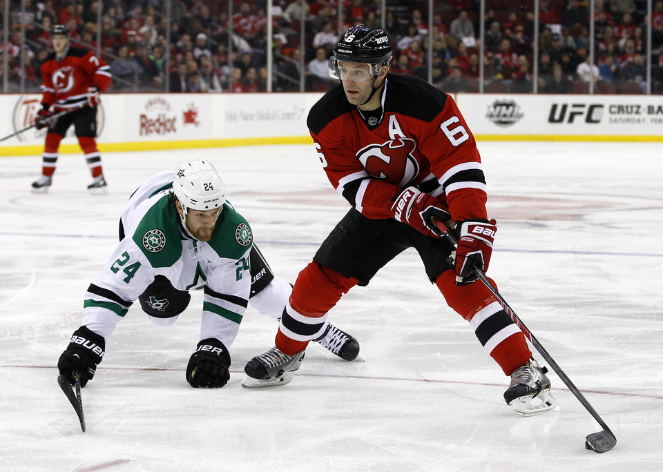 Photo - New Jersey Devils defenseman Andy Greene looks to pass the puck defended by Dallas Stars defenseman Jordie Benn during the second period of an NHL hockey game Thursday, Jan. 9, 2014, in Newark, N.J. (AP Photo/Adam Hunger)