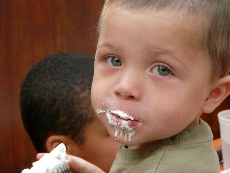 Cassius Mosby, 18 months, eats a cupcake Thursday at Norman's Community Thanksgiving Dinner.